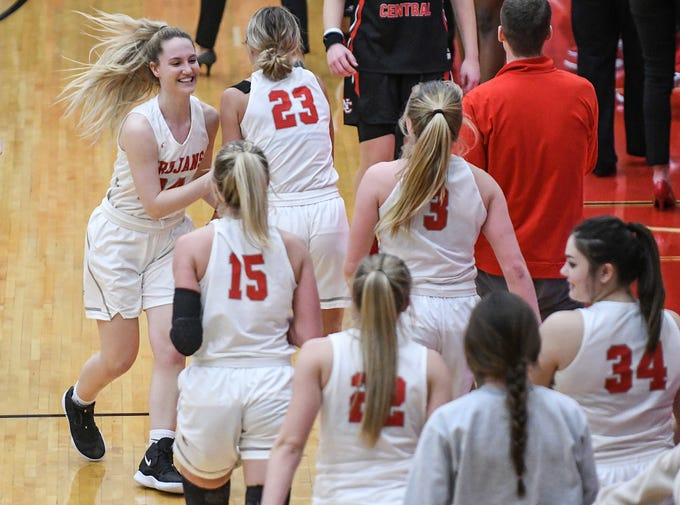 From left, Center Grove Trojans Emily Rake (24) celebrates with teammates after defeating North Central, 51-44, to reach a 15-game winning streak at Center Grove High School in Greenwood, Ind., Thursday, Jan. 10, 2019.