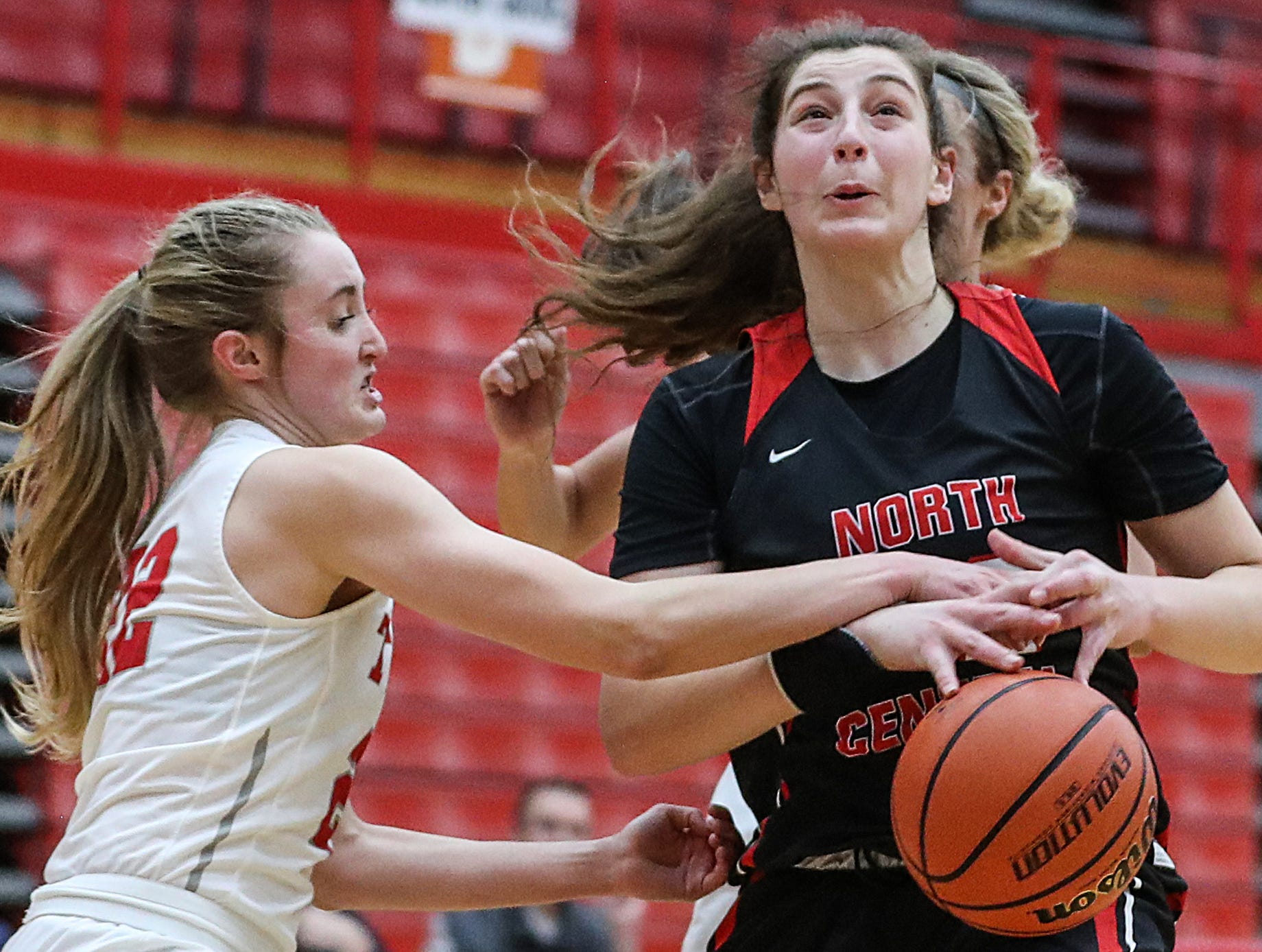 Center Grove Trojans Claire Rake (12) fouls North Central Panthers forward Meg Newman (42) in the second half of the game at Center Grove High School in Greenwood, Ind., Thursday, Jan. 10, 2019. Center Grove defeated North Central, 51-44.