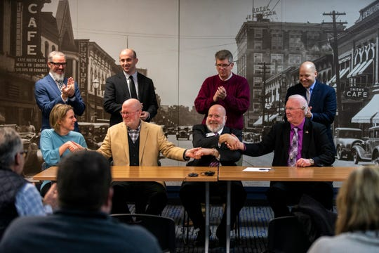 """Mayors Jim Throgmorton, of Iowa City, John Lundell, of Coralville, and Terry Donahue of North Liberty, shake hands after signing the """"Economic Development Communication Protocol"""" agreement on Friday, Jan. 11, 2019, at MERGE in downtown Iowa City, Iowa."""