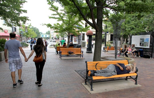 In this August 19, 2013 file photo, pedestrians shuffle through the ped mall with one individual sleeping on a bench.