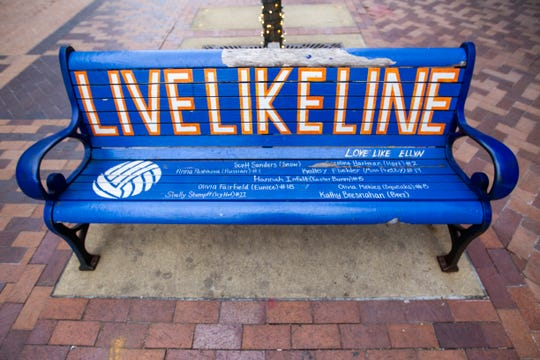 """A bench reading """"Live Like Line"""" in memory of Caroline Found, a West High volleyball player who died in 2011, is seen on Friday, Jan. 11, 2019, along the pedestrian mall in downtown Iowa City, Iowa. The city plans to remove this style of bench in its next phase of ped mall updates."""