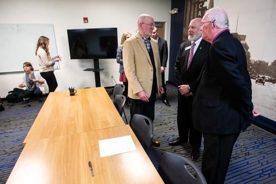 Mayors Jim Throgmorton, of Iowa City, John Lundell, of Coralville, and Terry Donahue of North Liberty, talk after signing a communication agreement on Friday, Jan. 11, 2019, at MERGE in downtown Iowa City, Iowa.