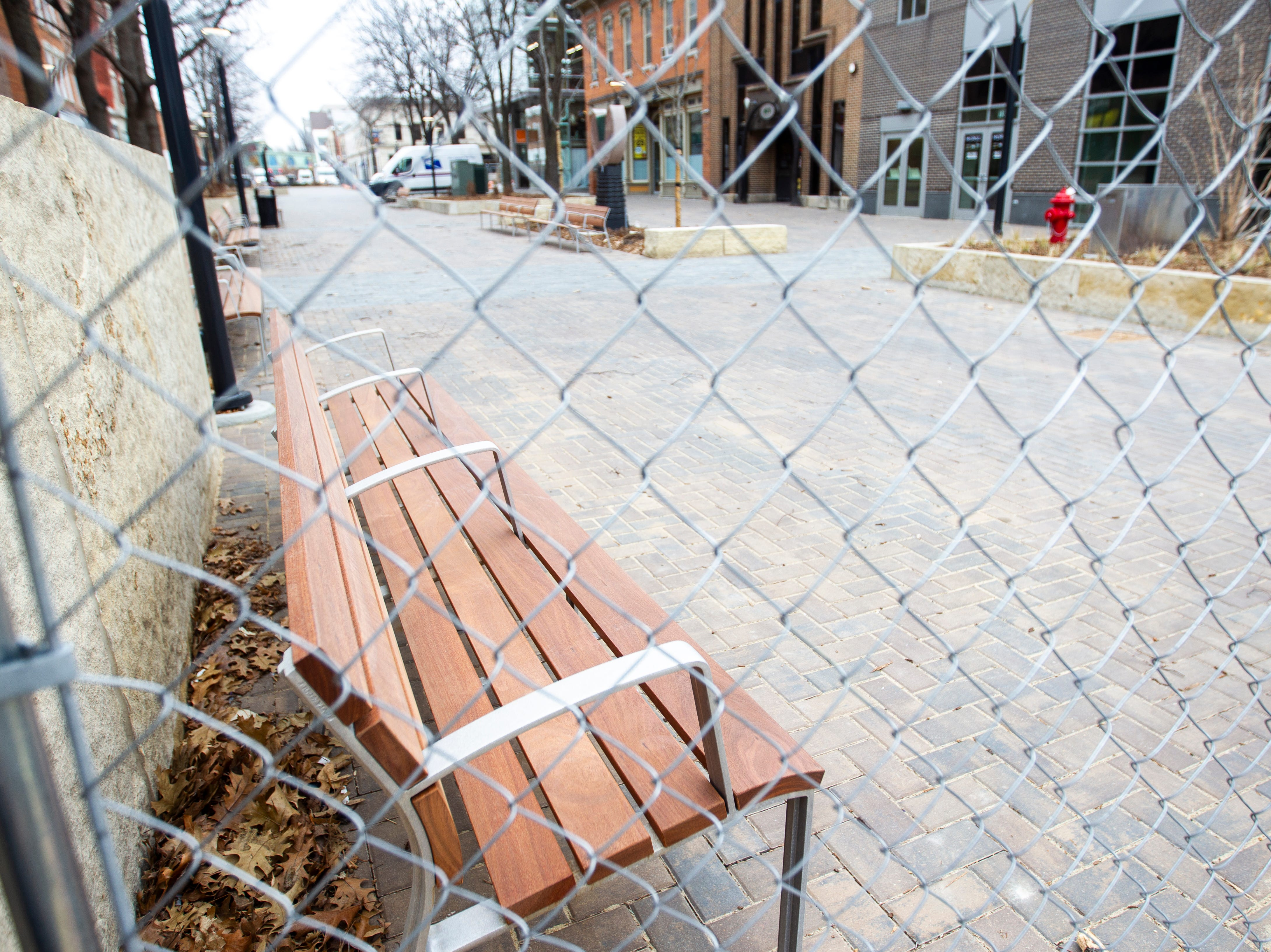 A new bench with handrails is seen through a chain link fence from construction on Friday, Jan. 11, 2019, along the pedestrian mall in downtown Iowa City, Iowa.