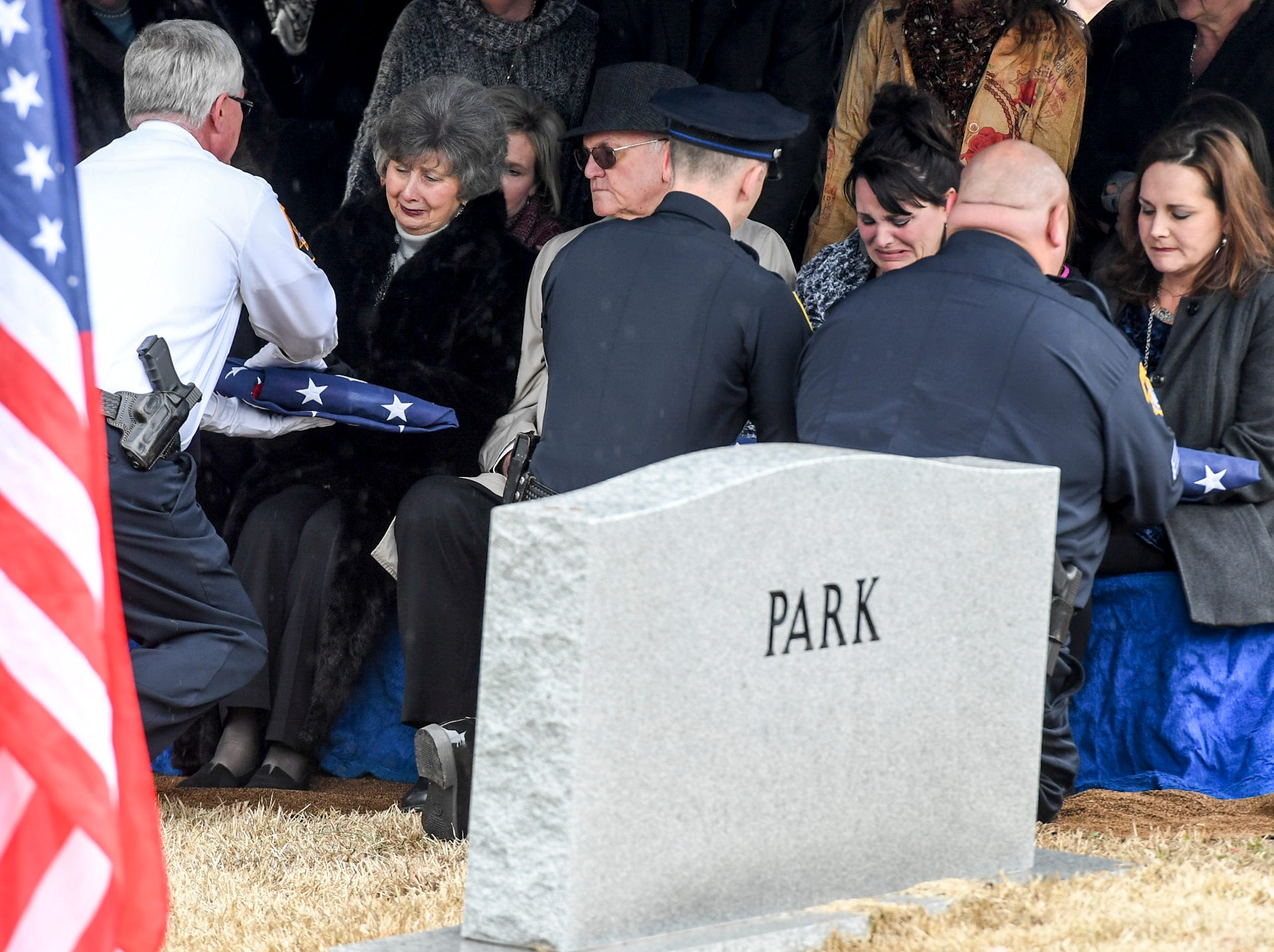 Law Enforcement officers hand folded American Flags to the mother and daughters, Becky, Elizabeth, and Phyllis, of Assistant Alamo Police Chief Phillip Harold Park at his burial service, Friday, Jan. 11, 2019.