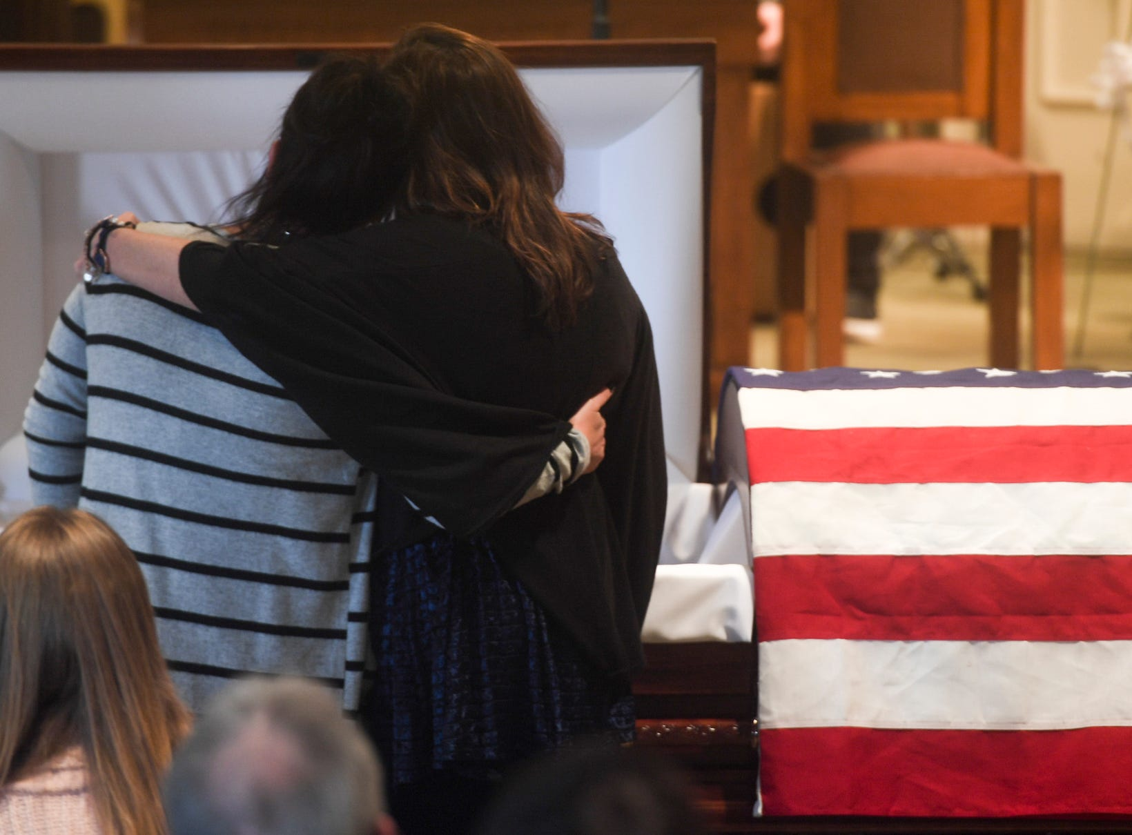Elizabeth and Phyllis Park console each other as they stand in front of their father's casket during the Celebration of Life service for Assistant Alamo Police Chief Phillip Harold Park, Friday, Jan. 11, 2019.