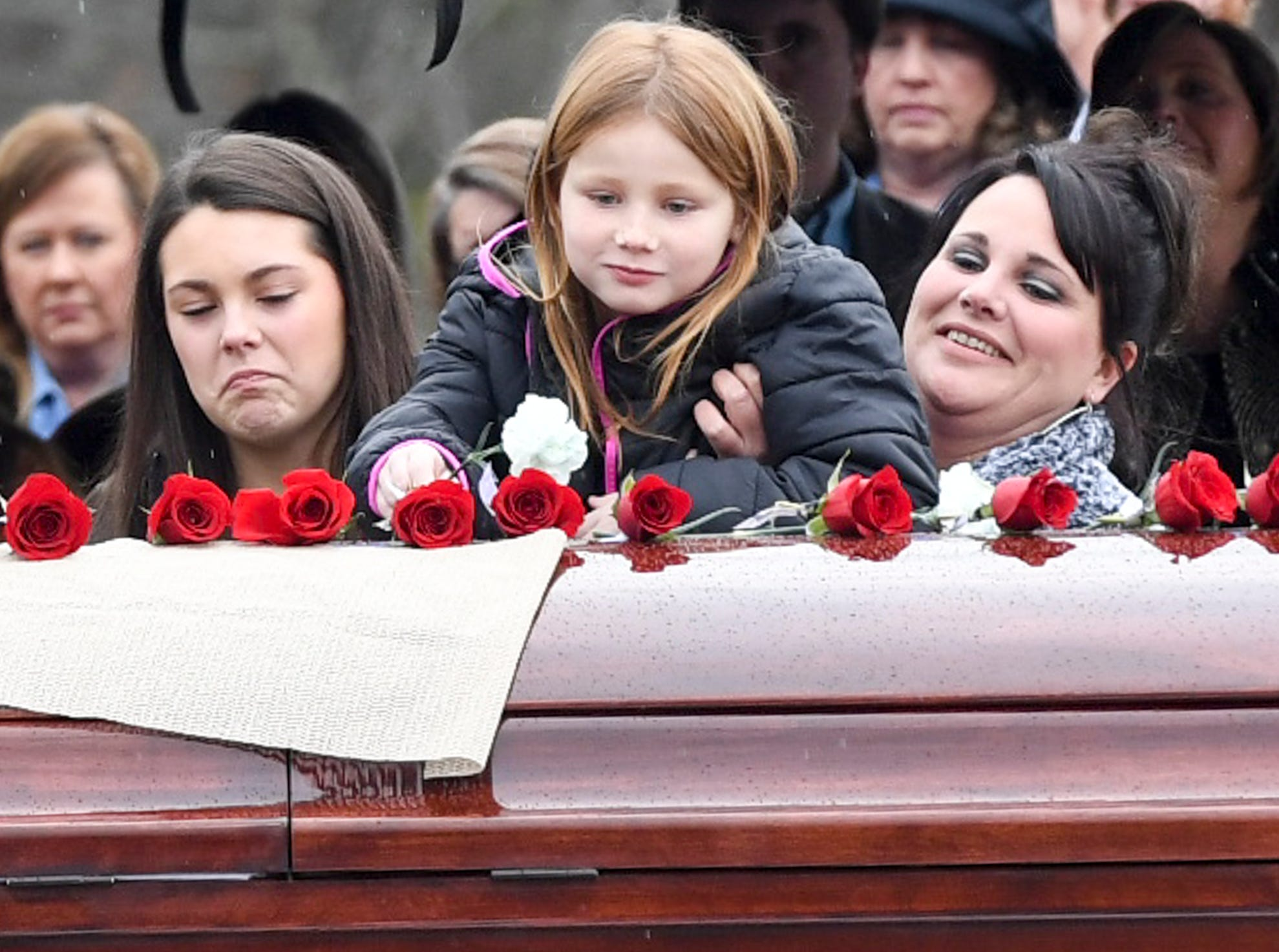 Allie Harber is held by her mother, Elizabeth, and joined by Ashton (and not picture Anna) as she places a flower on her grandfather Assistant Alamo Police Chief Phillip Harold Park's coffin during his burial service, Friday, Jan. 11, 2019.