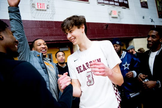 Bearden's Drew Pember is greeted by his future teammates from the Tennessee Volunteers Grant Williams, left, and Jordan Bowden, shaking hand, during a game between Bearden and Catholic at Bearden High School in Knoxville, Tennessee on Thursday, January 10, 2019.