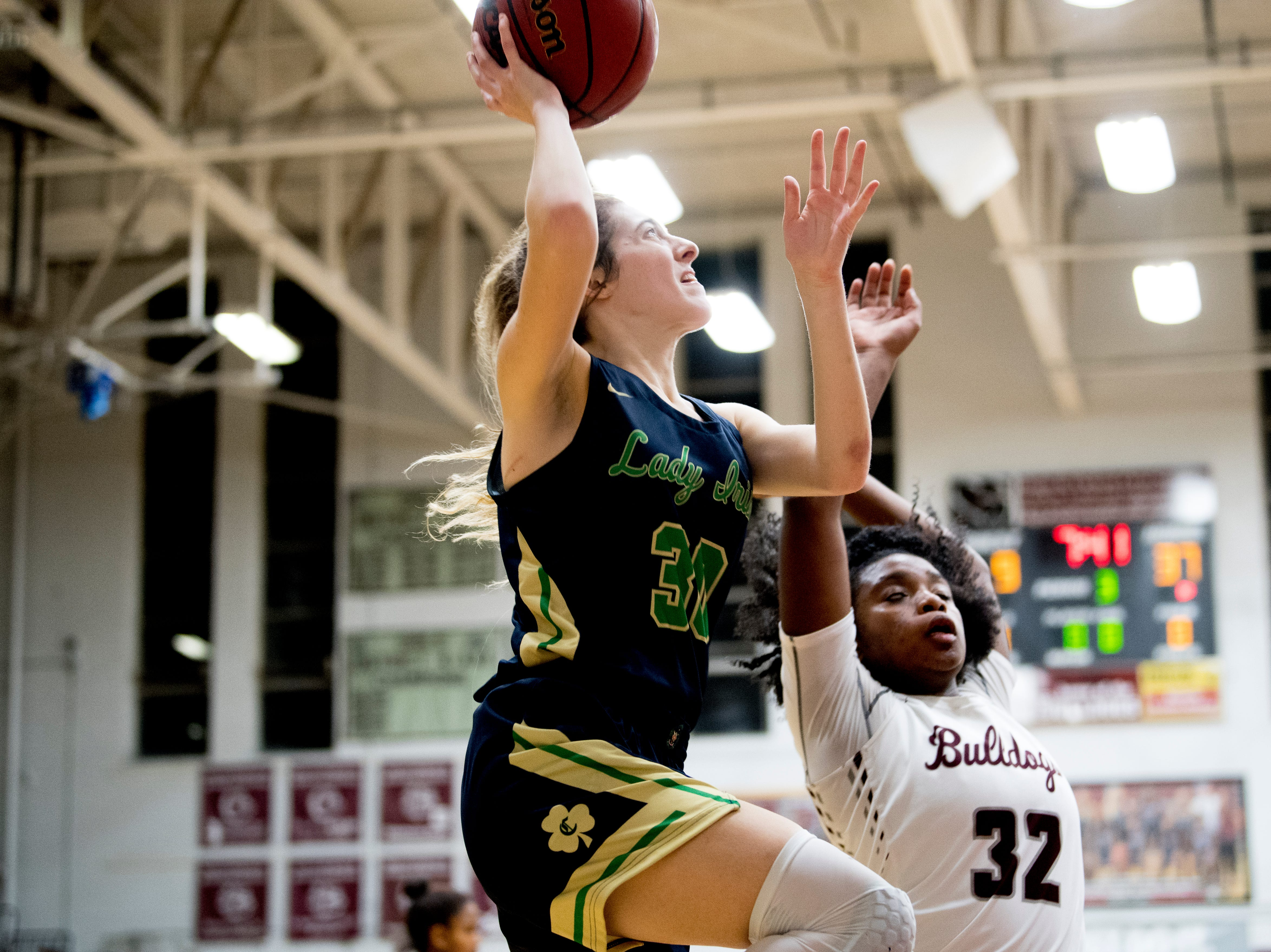 Catholic's Emily Pichiarella (30) goes for a layup as Bearden's Tytiaira Spikes (32) defends during a game between Bearden and Catholic at Bearden High School in Knoxville, Tennessee on Thursday, January 10, 2019.
