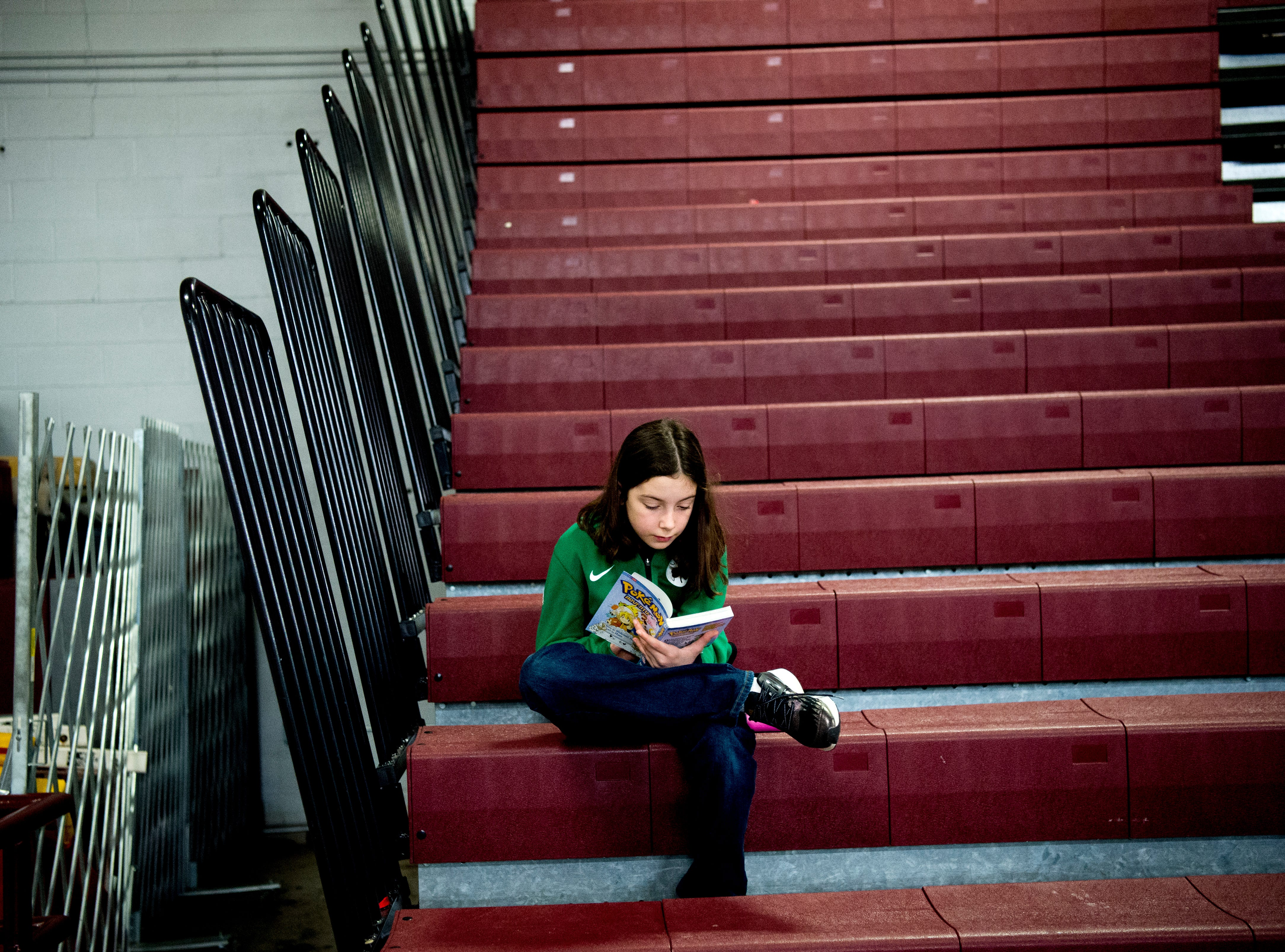 A girl finds a quiet space to read in the upper stands during a game between Bearden and Catholic at Bearden High School in Knoxville, Tennessee on Thursday, January 10, 2019.
