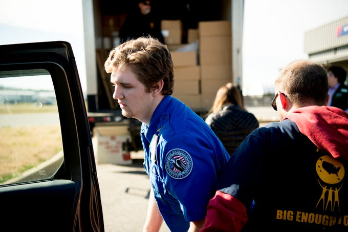 TSA agent Zachary Chapman loads up his back seat with meal boxes from Second Harvest Food Bank at McGhee Tyson Airport in Alcoa, Tennessee on Friday, January 11, 2019. Filling an 'unprecedented request,' Second Harvest Food Bank sent emergency food supplies to TSA workers.