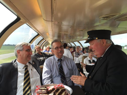In this June 2016 photo, Eric Holcomb, left, then Indiana's lieutenant governor, Arvid Olson, head of Greater Lafayette Commerce's transportation committee, talk with a Hoosier State employee as they ride from Indianapolis to Lafayette on the Hoosier State train. This week, Gov. Eric Holcomb proposed a budget that would cut $3 million a year earmarked for the Hoosier State.