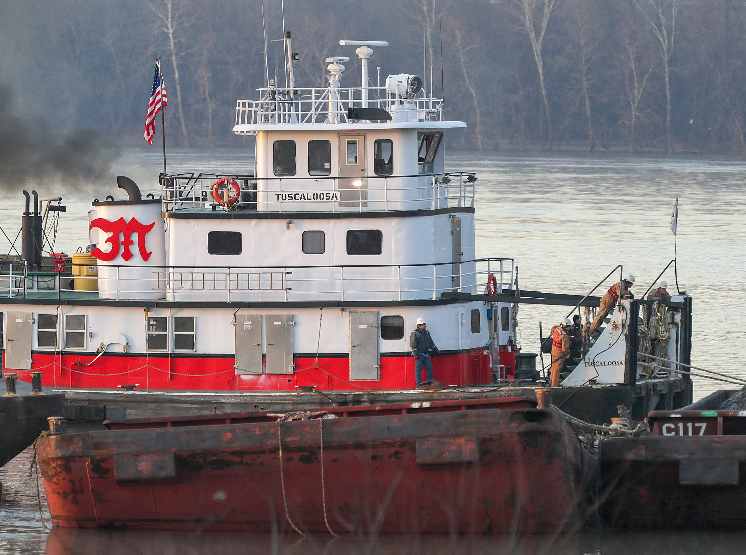 Crews continue to salvage coal-carrying barges that broke away after breaking free from a tow boat on Christmas day.  Seven of the barges have sunk and others are pinned by the current to the dam and spillway.
