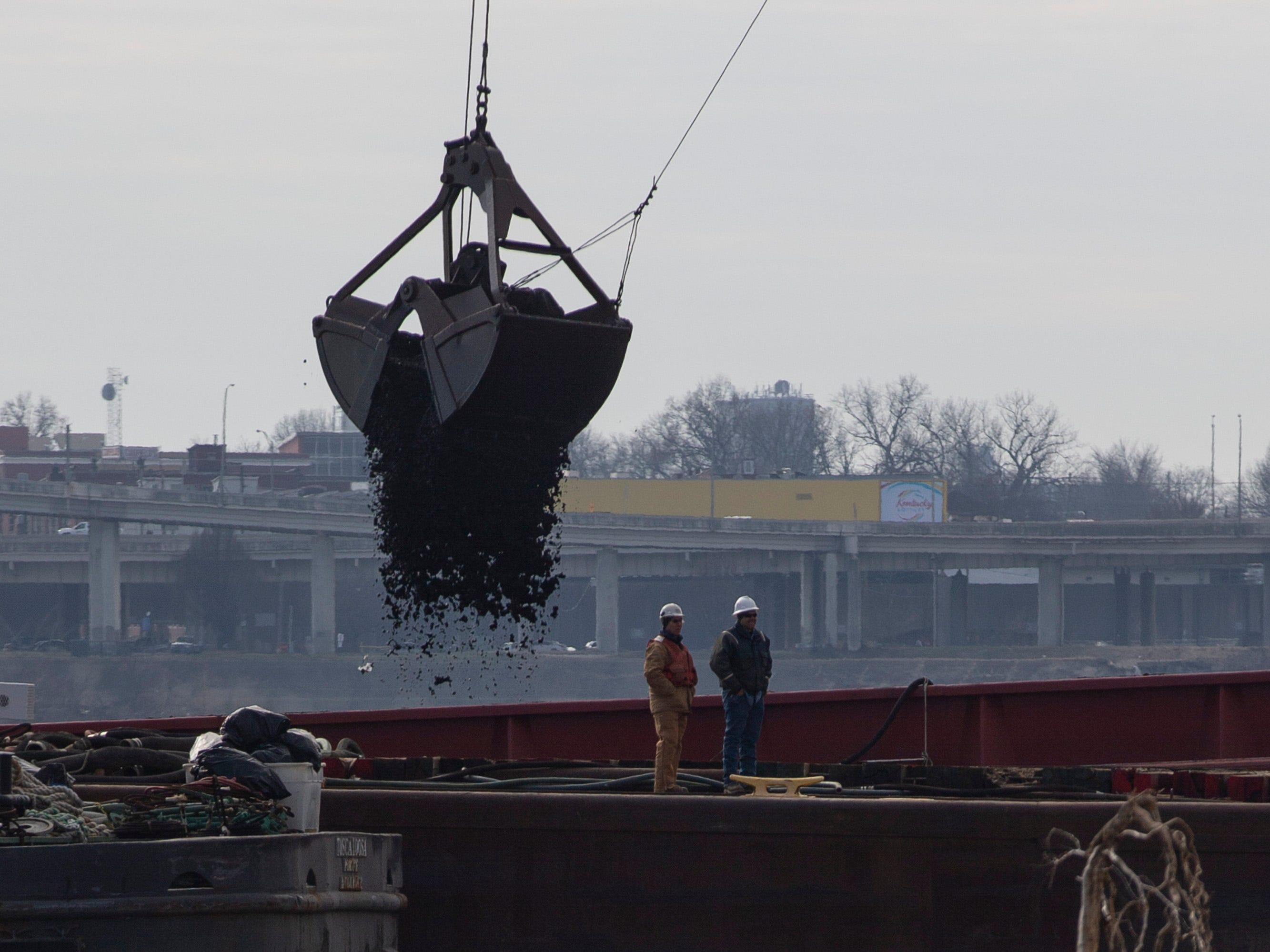Coal is recovered Friday from the first barge that will likely soon be attempted to be recovered from those stuck against the dam in Louisville. Jan. 11, 2019