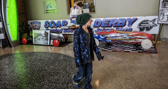 A youngster checks out the St. Johns Soap Box Derby display set up in the AgroLiquid building just outside of St. Johns Thursday, Jan. 10, 2109.
