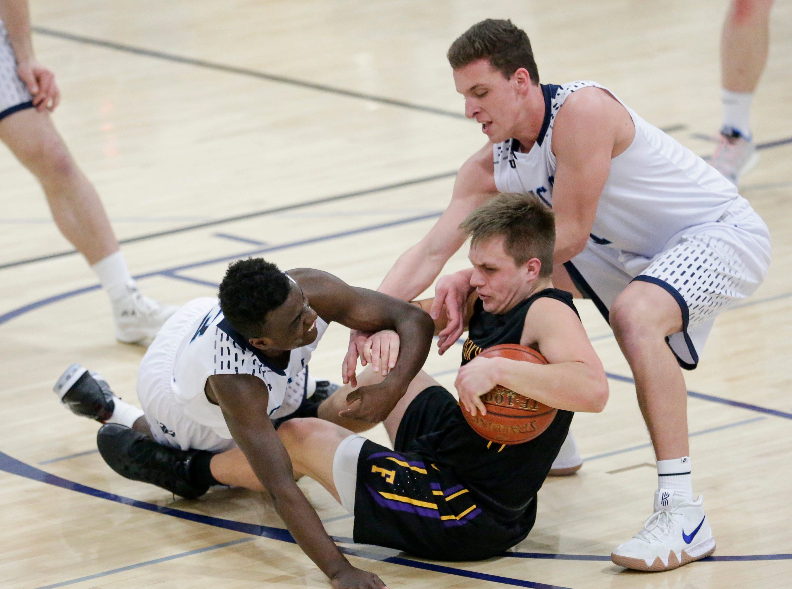 Sheboygan Falls' Alex Schmitt (2) tries to avoid a jump ball against Roncalli's Chombi Lambert (3) and Daniel Burgarino (1) during an EWC matchup at Roncalli High School Thursday, January 10, 2019, in Manitowoc, Wis. Joshua Clark/USA TODAY NETWORK-Wisconsin