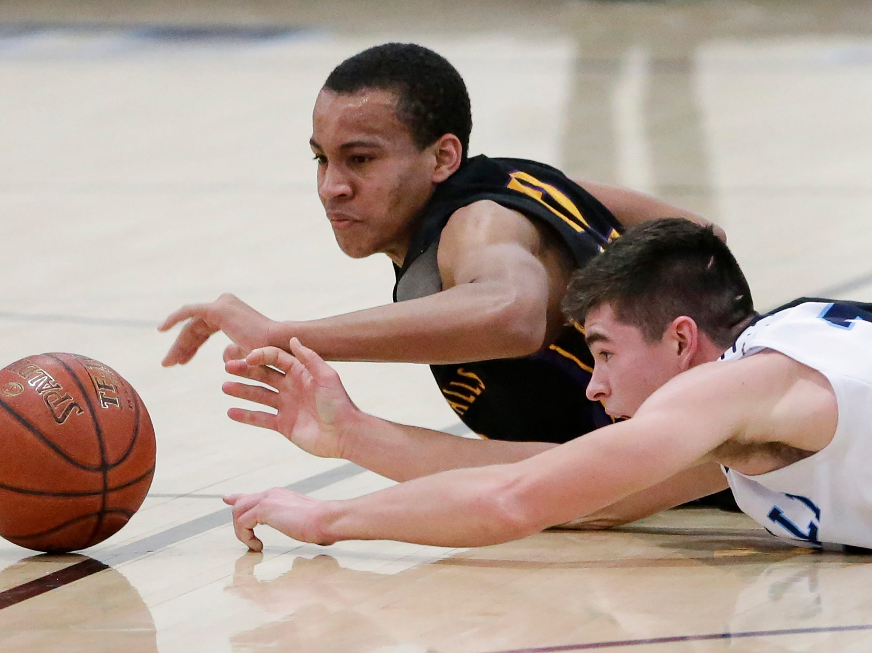 Sheboygan Falls' Dylan Grohskopf (32) battles Roncalli's Ian Behringer (34) for a loose ball during an EWC matchup at Roncalli High School Thursday, January 10, 2019, in Manitowoc, Wis. Joshua Clark/USA TODAY NETWORK-Wisconsin