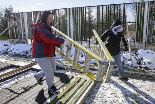 Manitowoc County drug court participants Jeni Eis, left, and Matthew Rocque carry a ladder to put a wall in place for Wildlife of Wisconsin rehabilitators Saturday, November 10, 2018, in Cato, Wis. Joshua Clark/USA TODAY NETWORK-Wisconsin