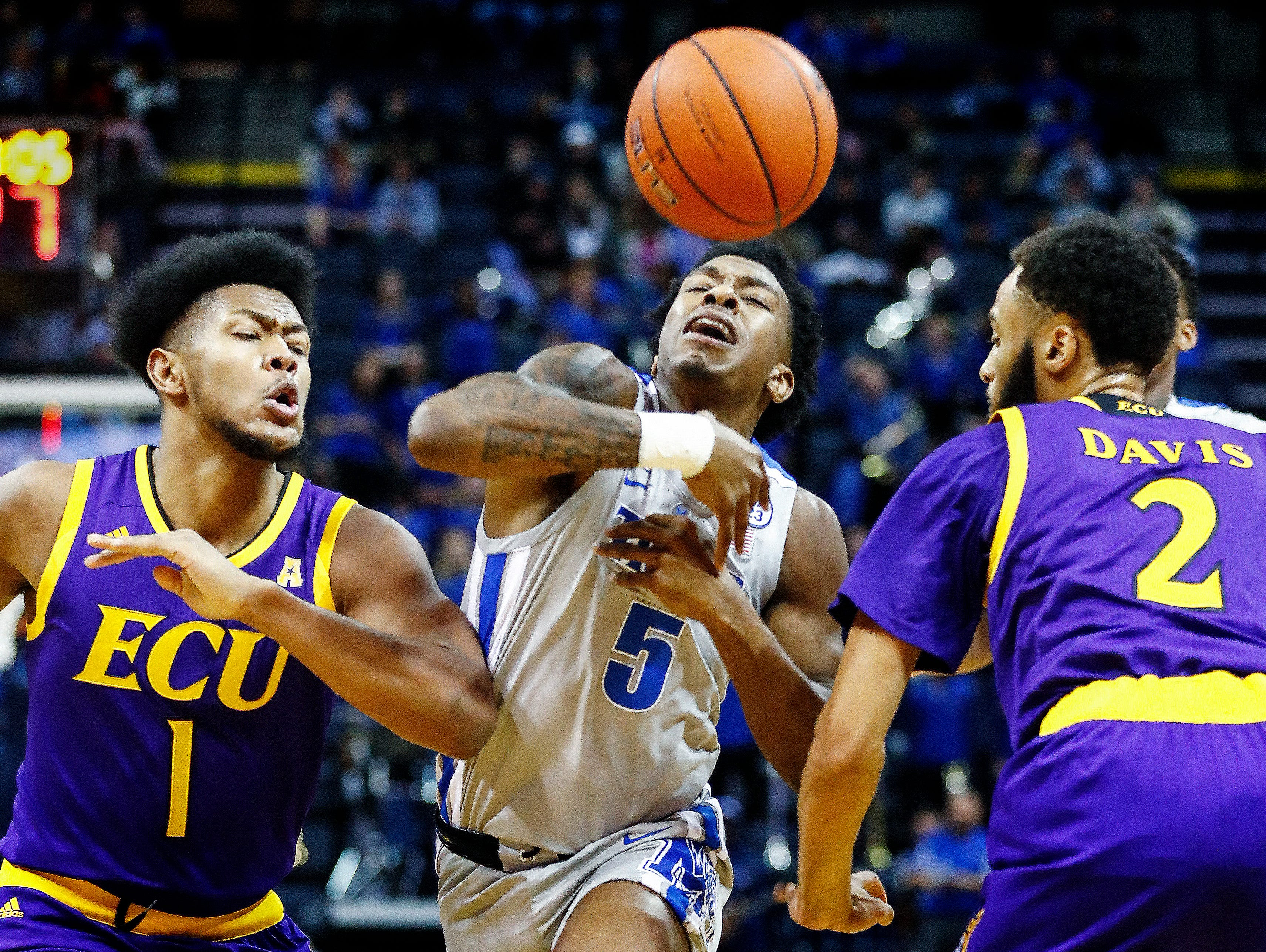 Memphis guard Kareem Brewton Jr. (middle) is fouled while driving the lane against ECU defenders Jayden Gardner (left) K.J. Davis (right) and during action at the FedExForum, Thursday, January 10, 2019.