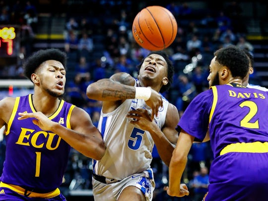 Memphis guard Kareem Brewton Jr. (middle) is fouled while driving the lane against ECU defenders Jayden Gardner (left) K.J. Davis (right).