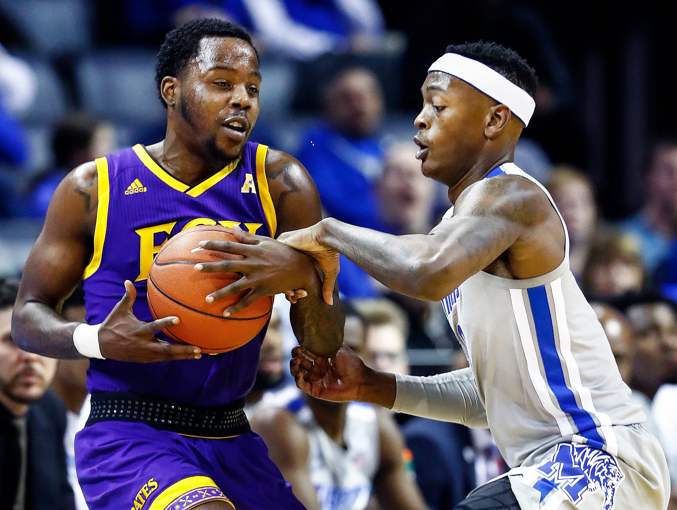 Memphis defender Kyvon Davenport (right) applies defensive pressure to ECU guard Isaac Fleming (left) during action at the FedExForum, Thursday, January 10, 2019.