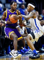 Memphis defender Kyvon Davenport (right) applies pressure to ECU guard Isaac Fleming.