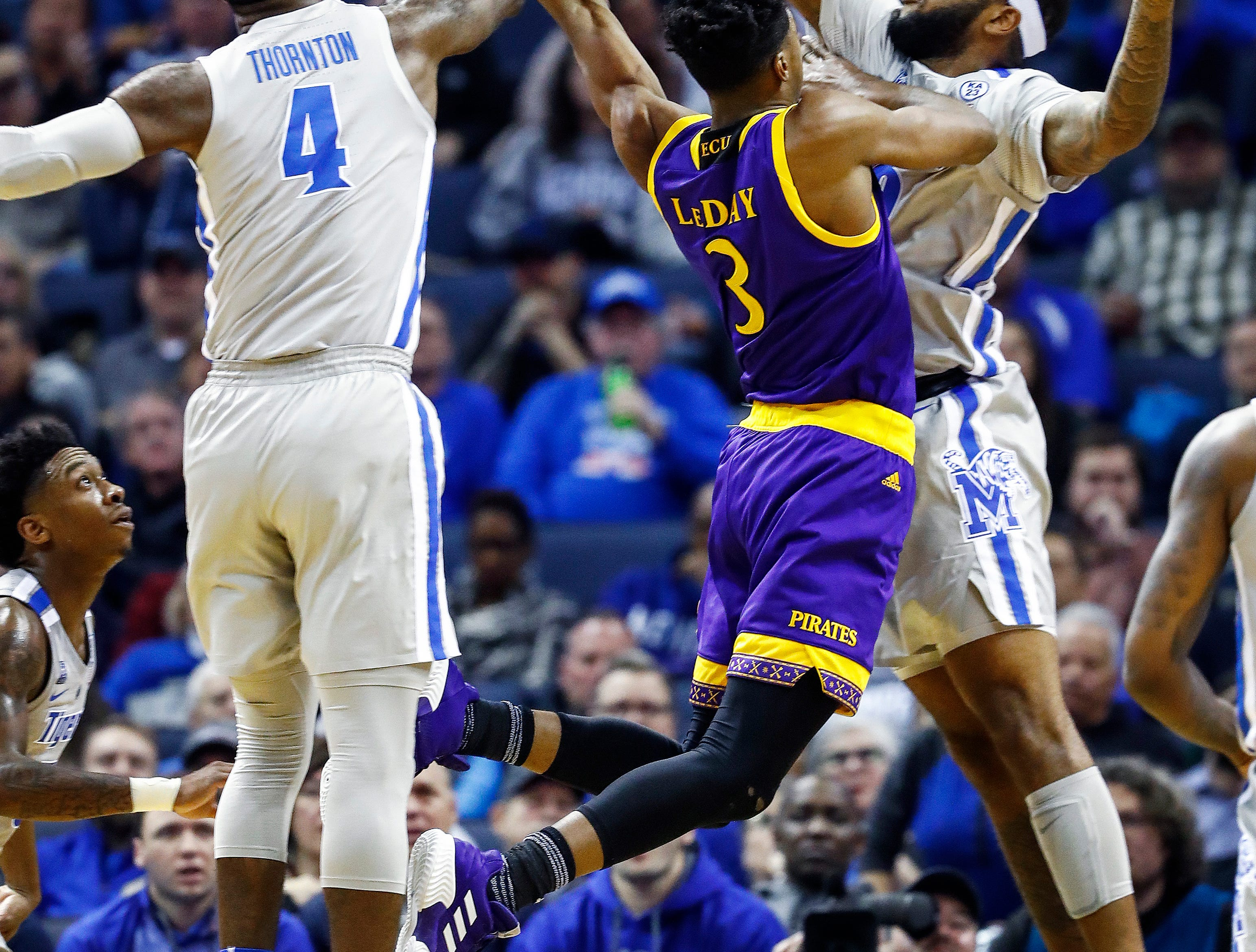 Memphis defenders Raynere Thornton (left) and Mike Park Sr. apply defensive pressure to the shot of ECU forward Seth LeDay (middle) during action at the FedExForum, Thursday, January 10, 2019.