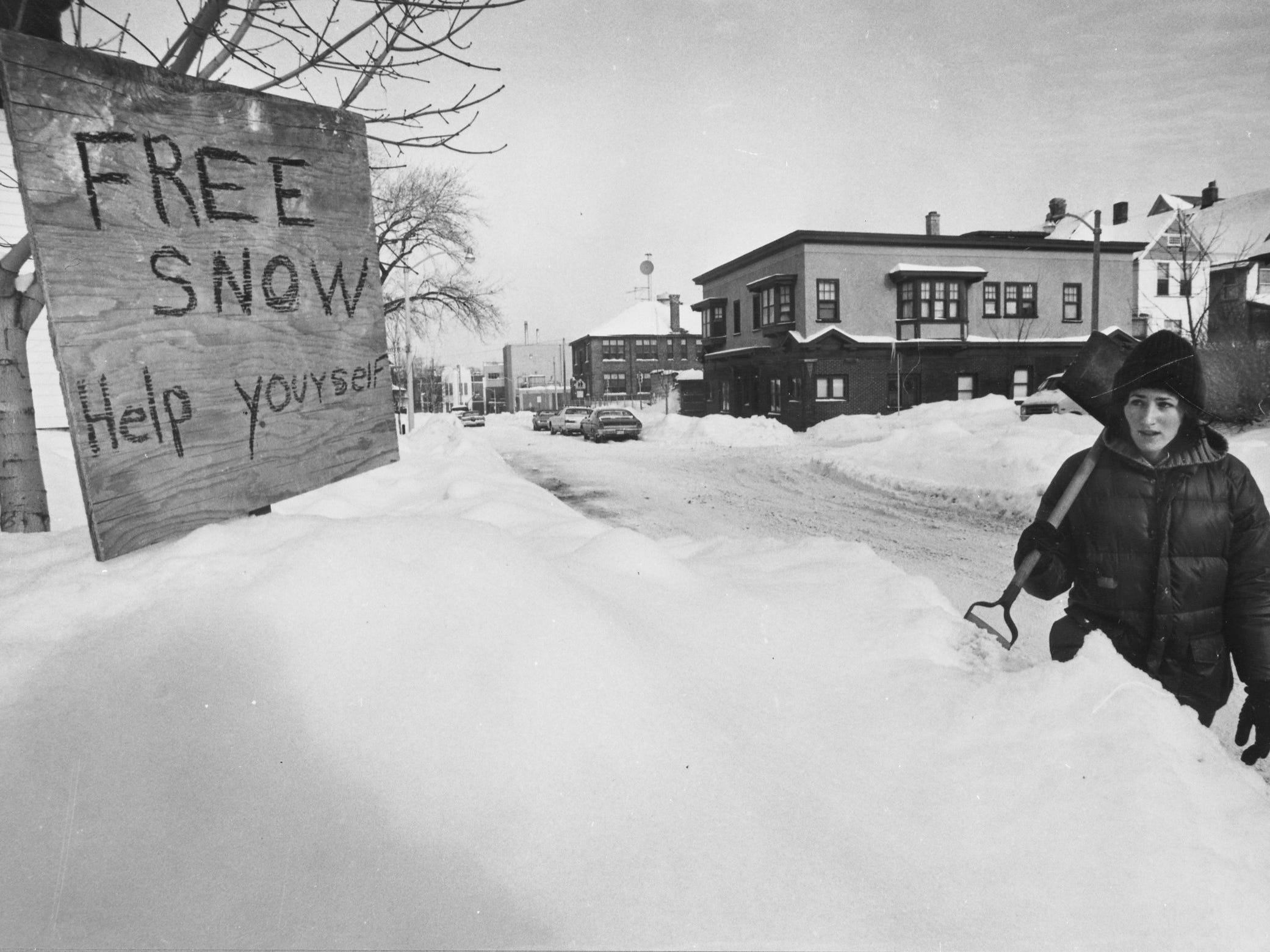 "Marianne San Felippo looks as if she's hoping there'll be some takers as she walks by a ""Free Snow - Help Yourself"" sign in the 1900 block of North Bartlett Avenue on Jan. 16, 1979. Milwaukee was in the midst of digging out of the second major snowstorm in two weeks, with another on the way. This photo was published in the Jan. 17, 1979, Milwaukee Journal."