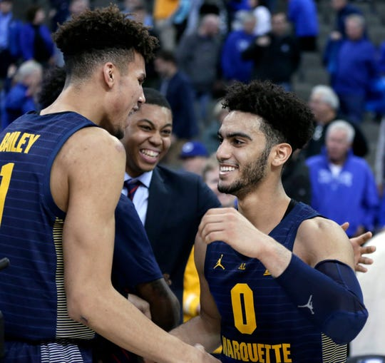 Marquette's Markus Howard celebrates with teammates Brendan Bailey (left) and Greg Elliott after Howard's 53-point performance on Wednesday.