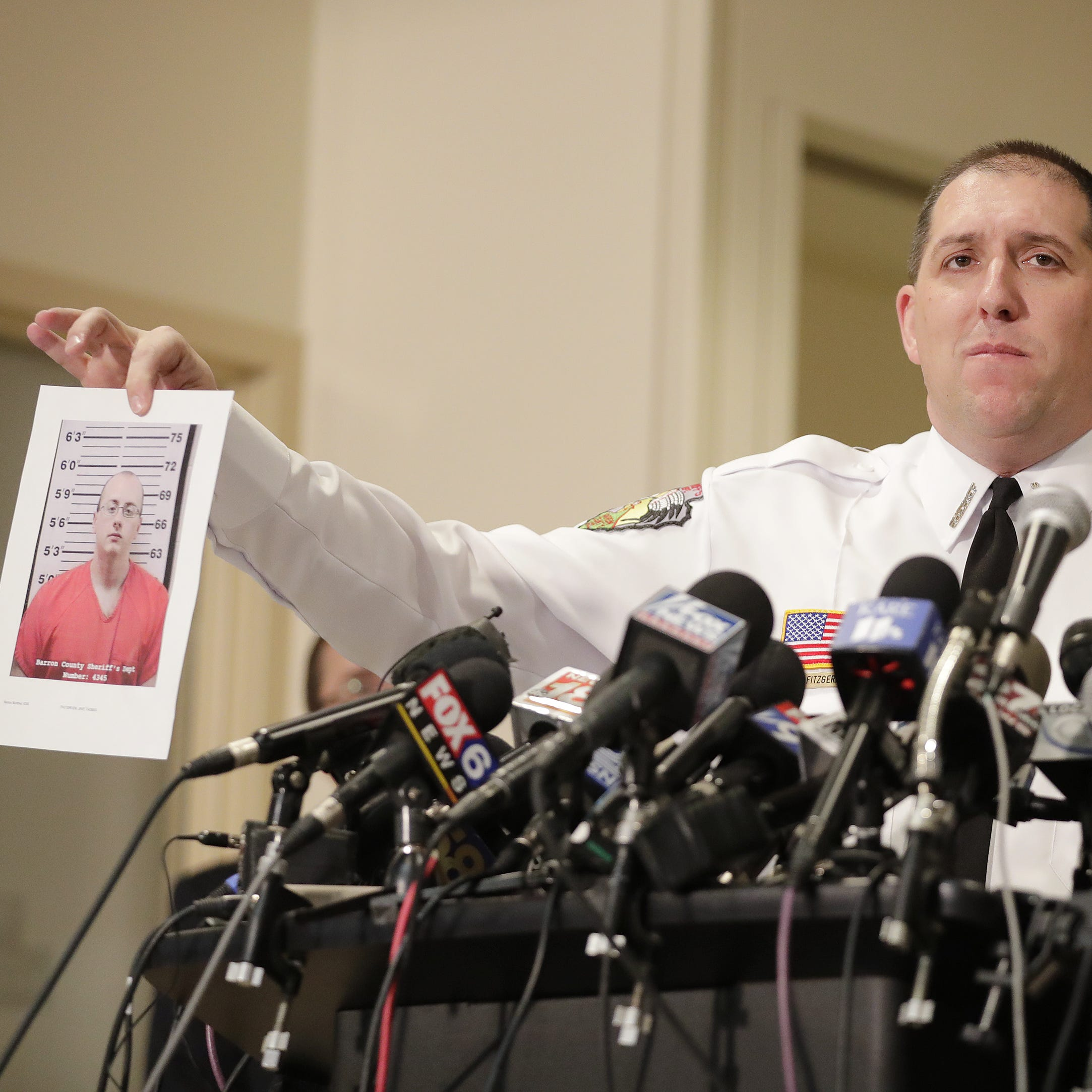 Barron County Sheriff Chris Fitzgerald holds up a photo of the suspect in custody in the kidnapping of Jayme Closs, 13, during a news conference at the Sheriff's Department on Friday.  Jayme was found near the Town of Gordon in northern Wisconsin on Thursday. She  had been missing since Oct. 15, the same day her parents, James, 56, and Denise, 46, were found shot to death in their home outside Barron.