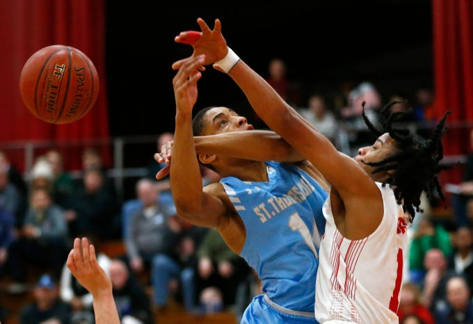 St. Thomas More's Eric Williams is fouled by St. Francis' Perrion Oliphant at St. Francis on Jan. 10.