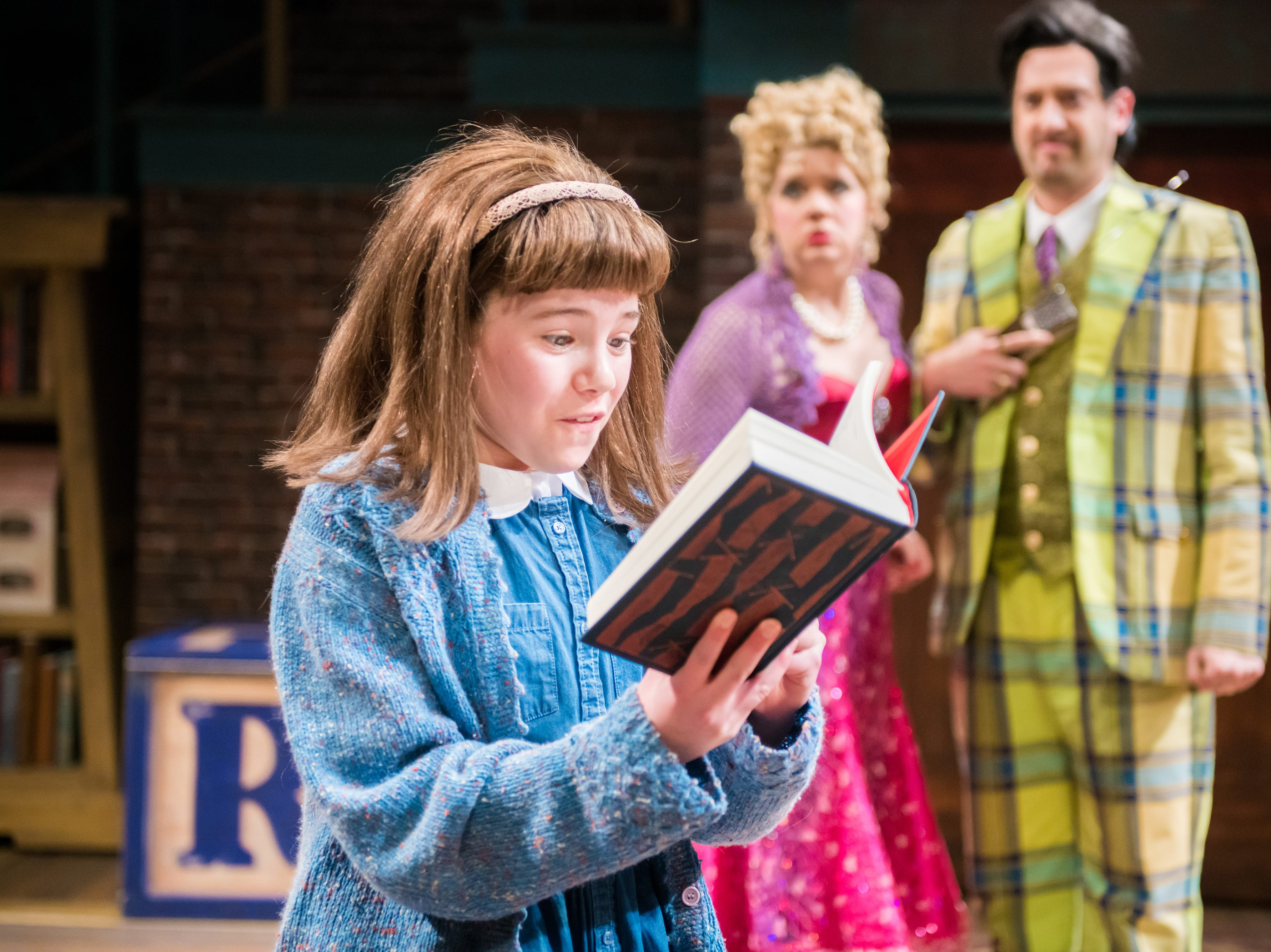 """Reese Bell (left) enjoys reading, to the chagrin of Molly Rhode and Jackson Evans in First Stage's """"Matilda,"""""""