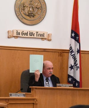 County Judge Mickey Pendergrass holds a copy of the county's 2017 financial and compliance report assembled by the Arkansas Legislative Audit.