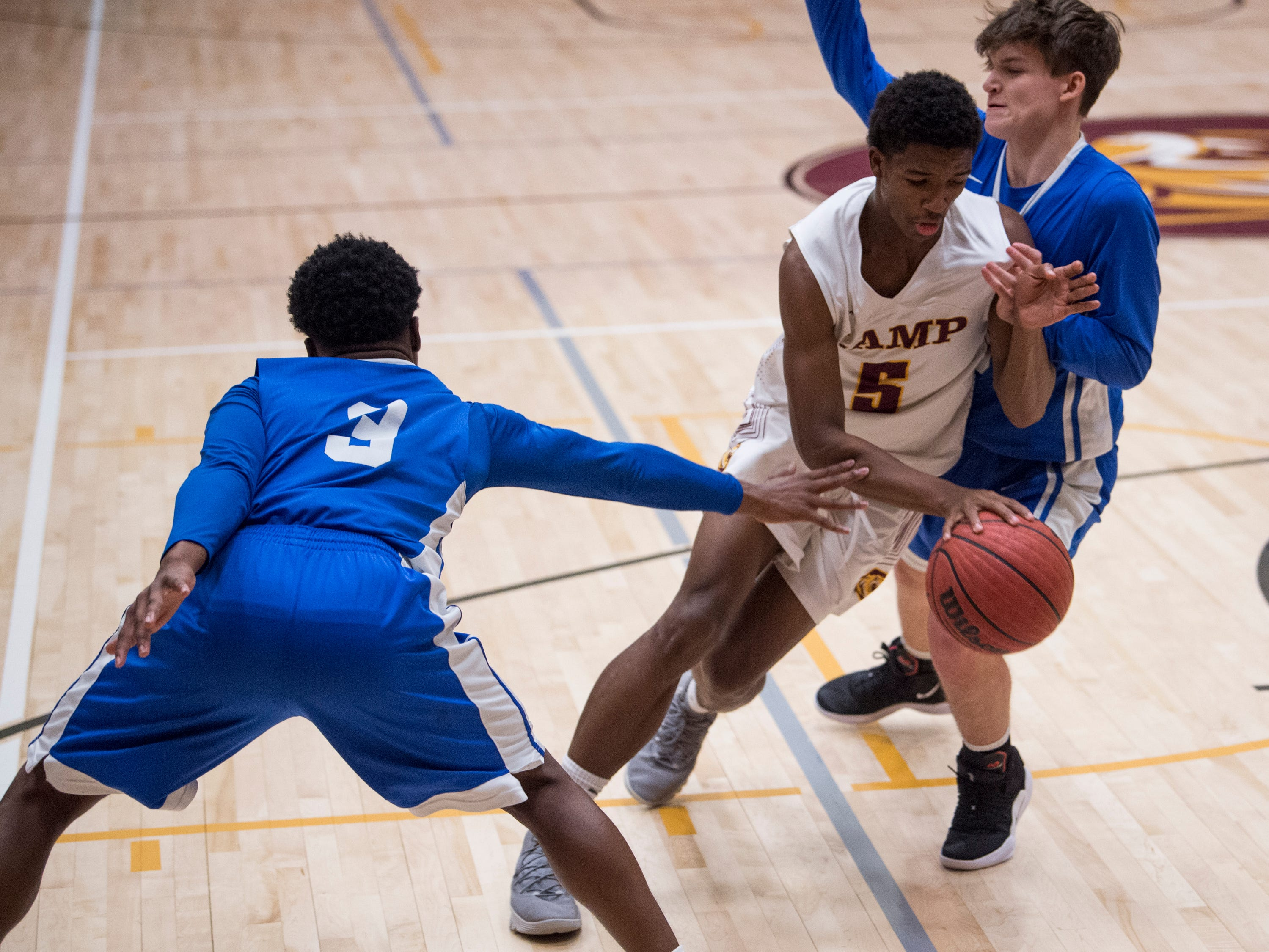 LAMP's Christopher Graham, middle, drives on Marbury's Chase Caver at LAMP high school in Montgomery, Ala., on Thursday, Jan. 10, 2019. LAMP defeated Marbury 85-72.