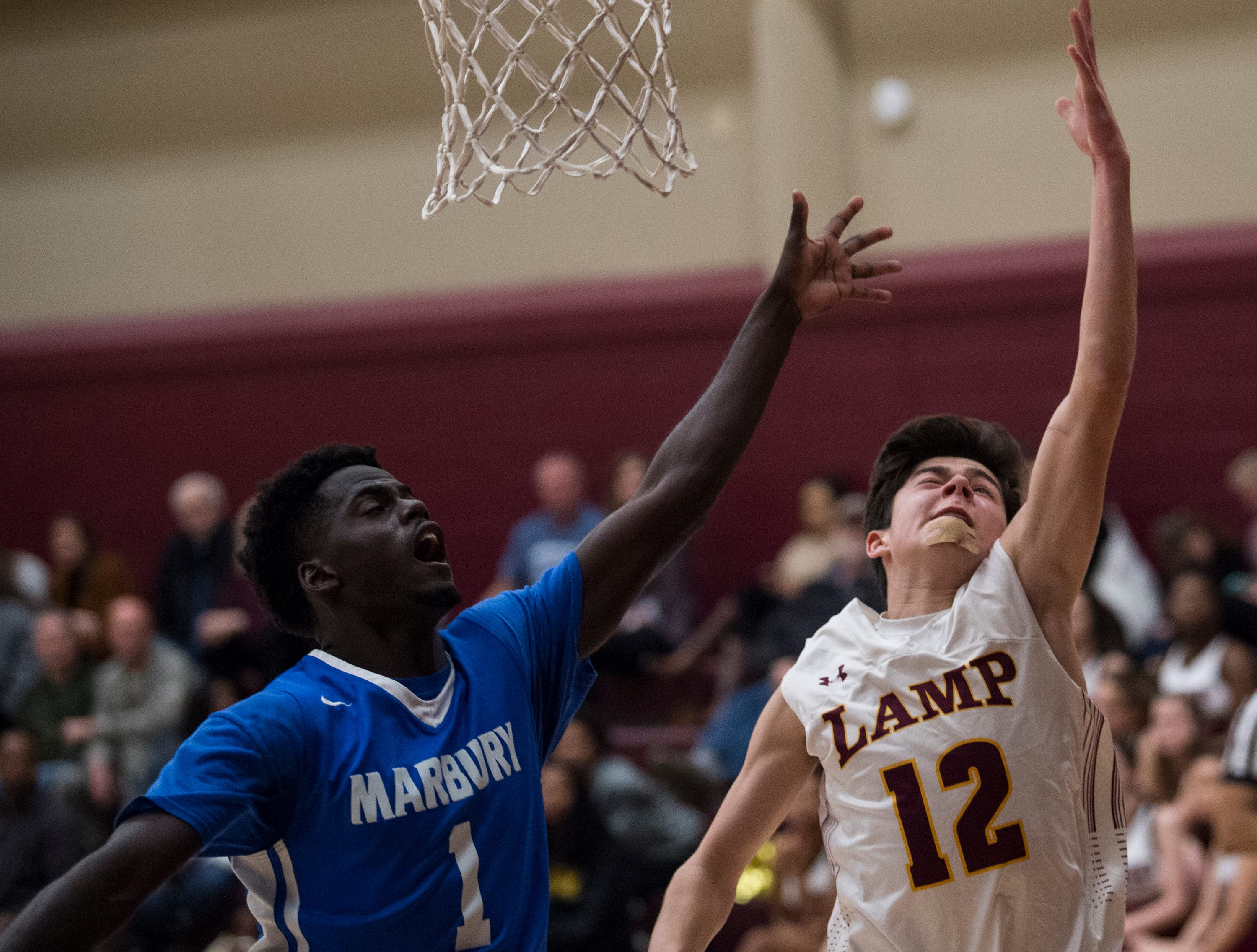 LAMP's Mitchell Sloane (12) goes up for a layup over Marbury's Jakhiel Waller (1) at LAMP high school in Montgomery, Ala., on Thursday, Jan. 10, 2019. LAMP defeated Marbury 85-72.