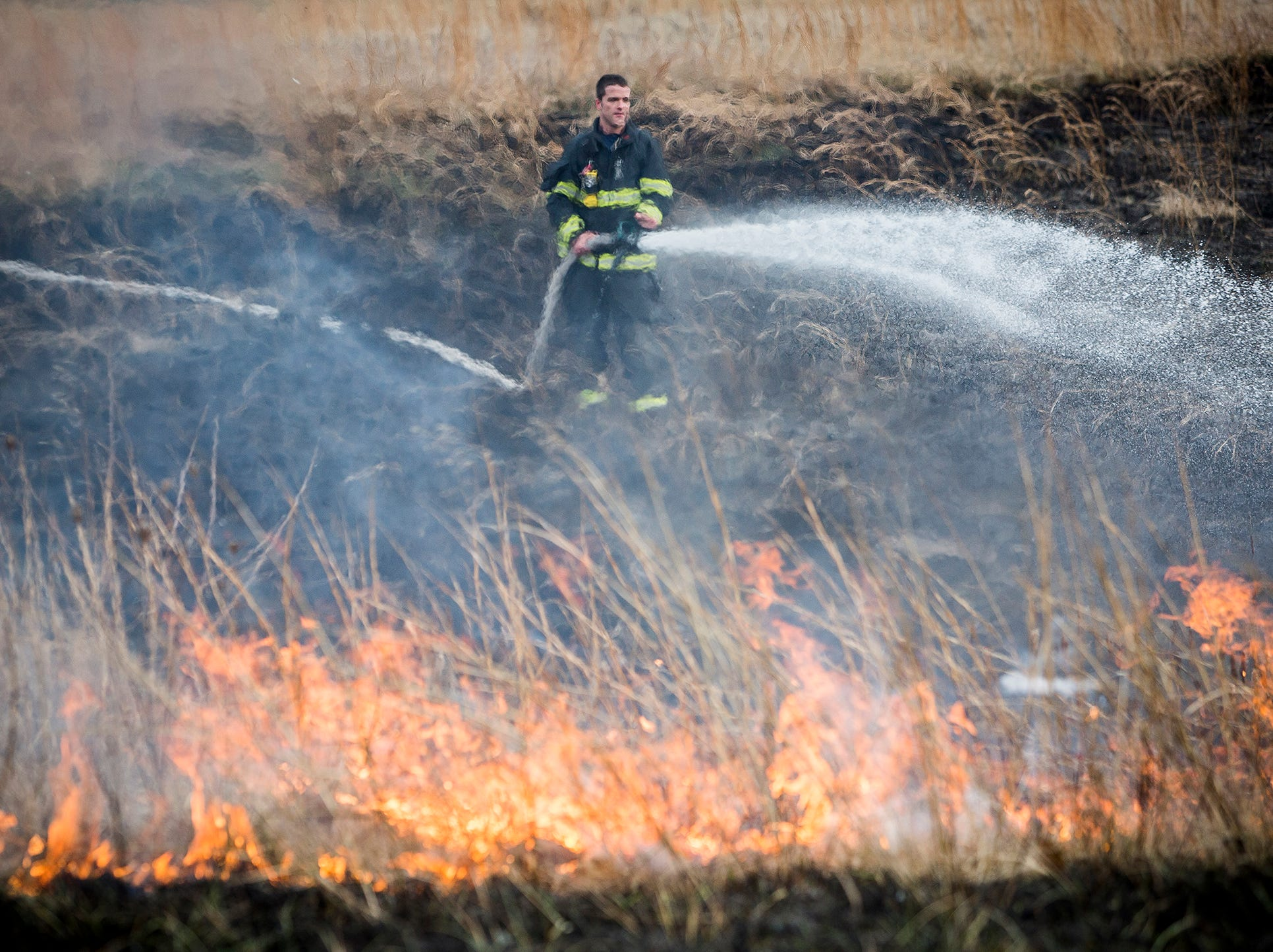 Monroe Township firefighters stop the spread of  multiple field fires along State Road 67 at locations north and south of the Muncie Bypass shortly after 3 p.m. Friday. According to Fire Chief Greg Hudson  the cause of the fires, which were spread at various locations along 67 including sections of the median, is indeterminate. None of the witnesses who reported the incident saw the fires start. Fire trucks were positioned between the burning fields and nearby houses as a precaution.