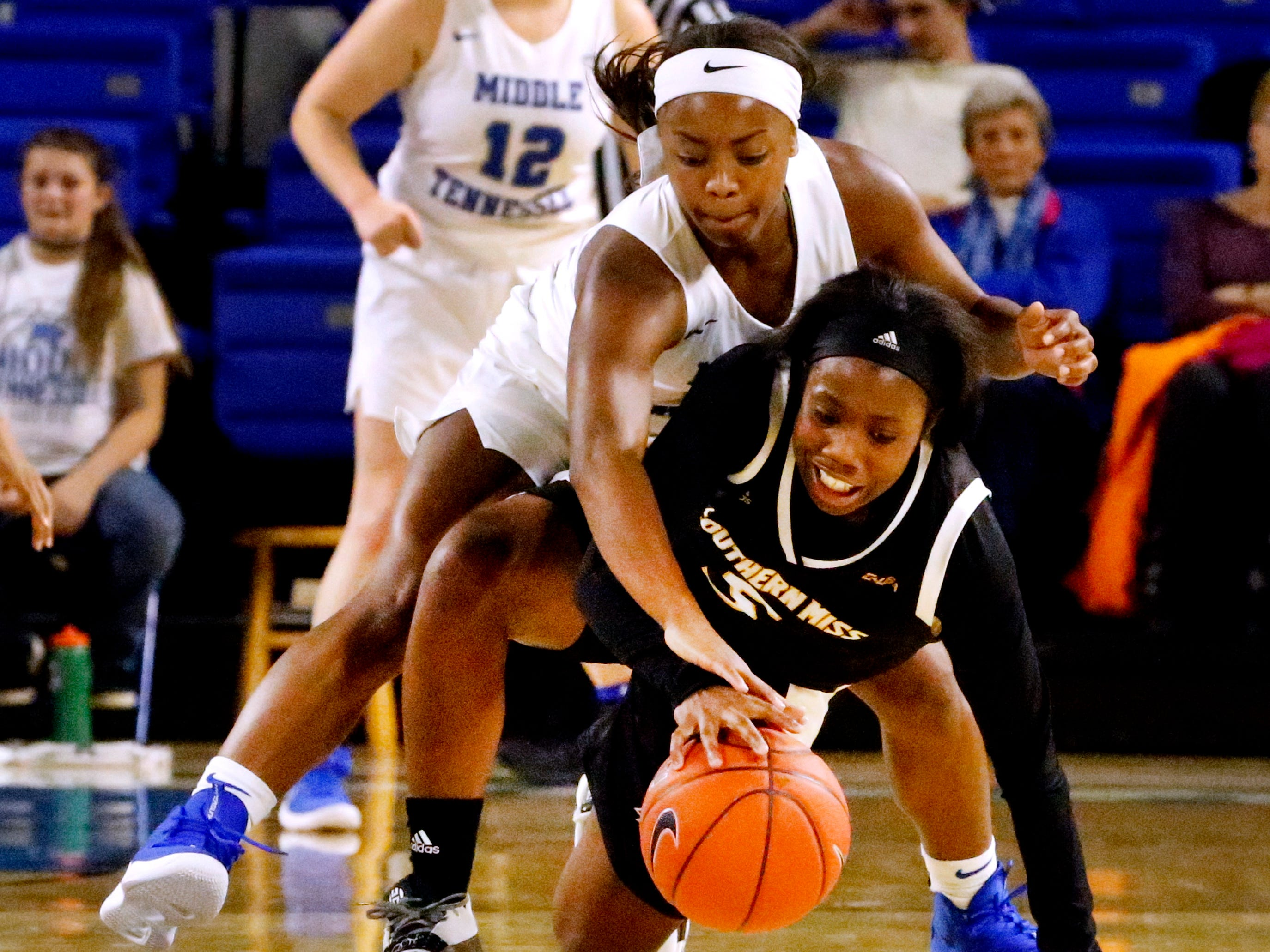 Southern Miss' Shonte Hailes (5) falls to the ground while dribbling as MTSU's guard Taylor Sutton (2) tries to steal the ball away, on Thursday Jan. 10, 2019.