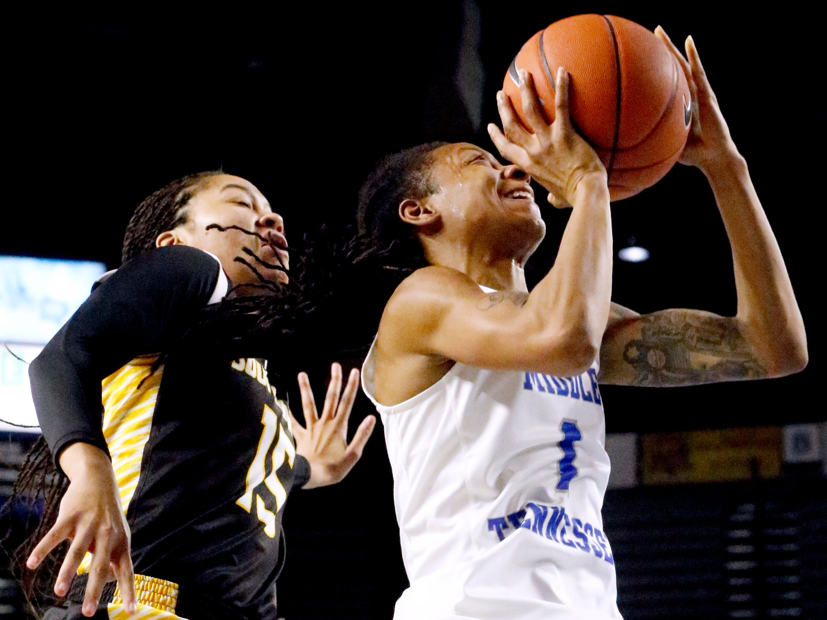 MTSU's guard A'Queen Hayes (1) goes up for a shot as Southern Miss' Amber Landing (15) comes up from behind her, on Thursday Jan. 10, 2019.