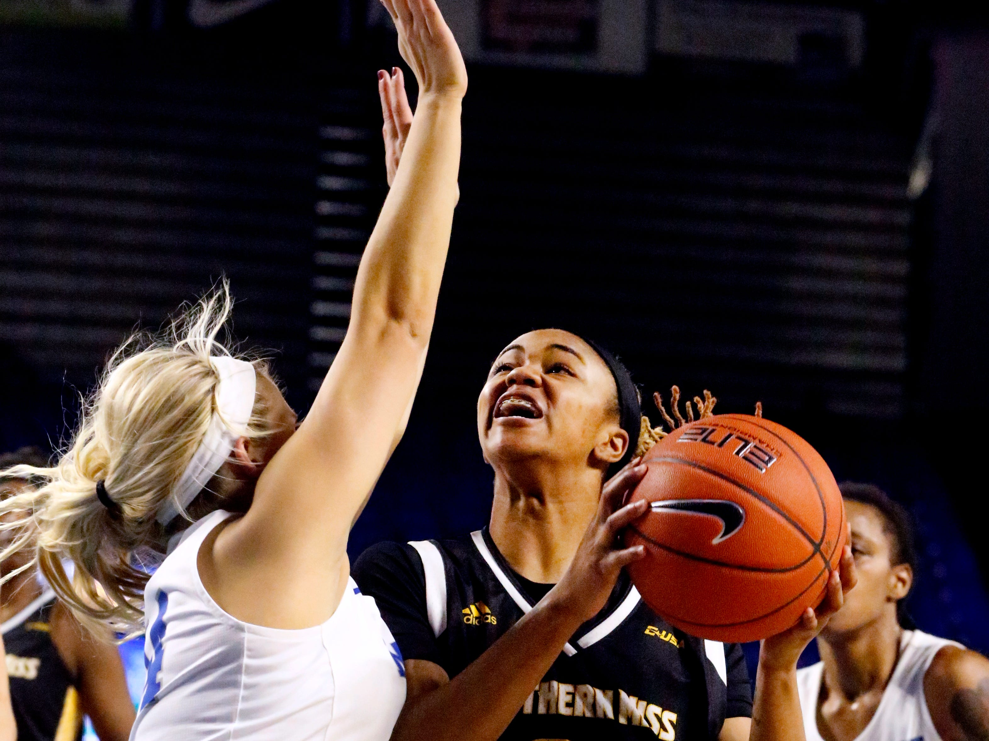 Southern Miss' Daishai Almond (21) goes for a shot as MTSU's guard Katie Collier (14) guards her, on Thursday Jan. 10, 2019.
