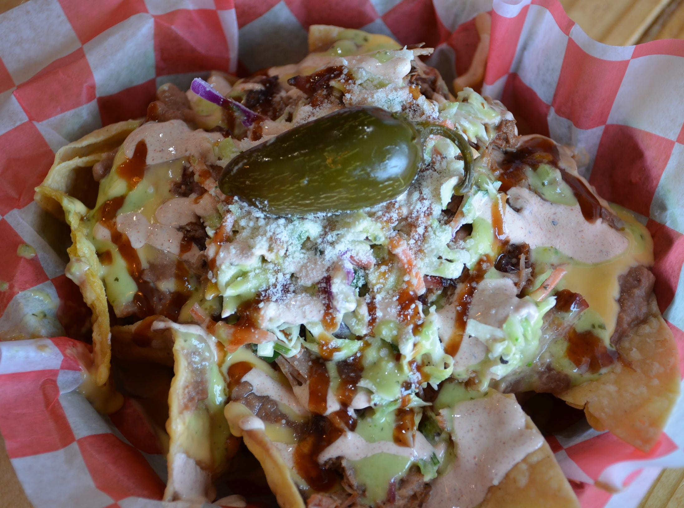 Nachos at The Meat Sweats BBQ includes smoked pulled pork, pico cole slaw, beans, nacho cheese, salsa, Mexican cotija cheese and a jalapeno.