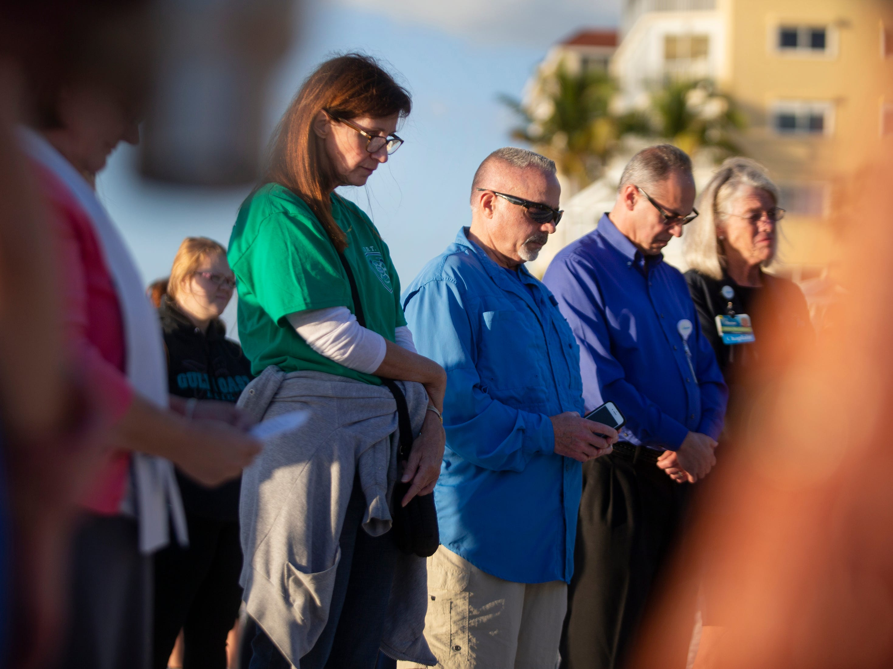 Community members observe a moment of silence to honor local children who have died in a drowning accident during a the 6th Annual Twin Tot Walk Vigil, Friday, Jan. 11, 2019 at Vanderbilt Beach.