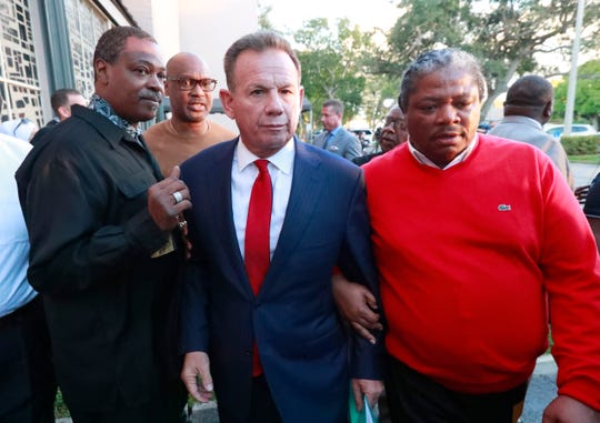Suspended Broward County Sheriff Scott Israel, center, leaves a news conference surrounded by supporters Friday, Jan. 11, 2019, in Fort Lauderdale, Fla., after new Florida Gov. Ron DeSantis suspended him, over his handling of last February's massacre at Marjory Stoneman Douglas High School. (AP Photo/Wilfredo Lee)