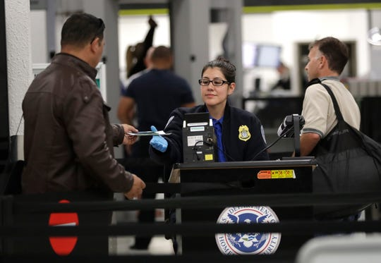 A Transportation Security Administration officer works at a checkpoint at Miami International Airport, Sunday, Jan. 6, 2019, in Miami.