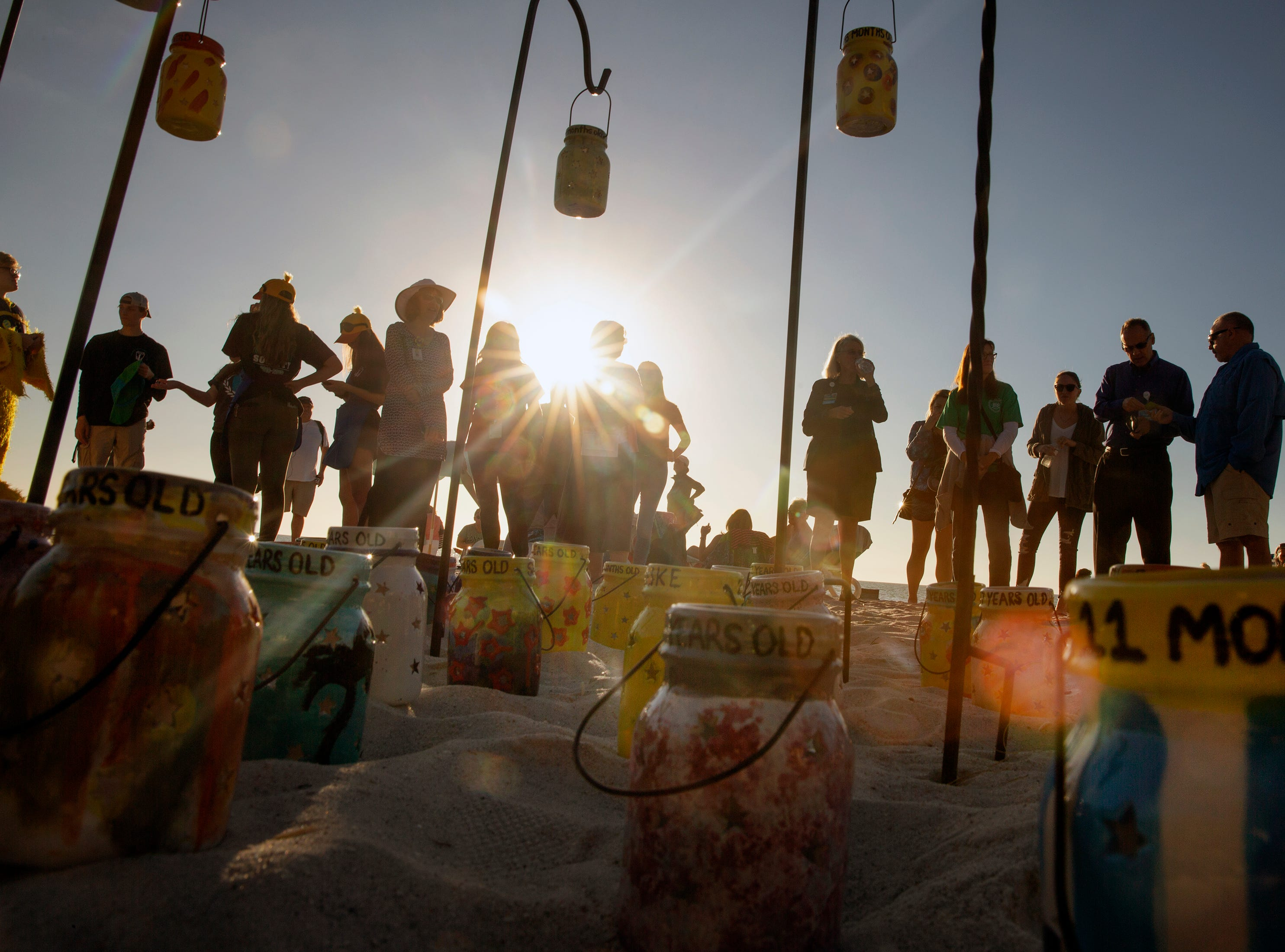 Community members gather around lanterns to honor local children who have died due to drowning during the 6th Annual Twin Tot Walk Vigil, Friday, Jan. 11, 2019 at Vanderbilt Beach.