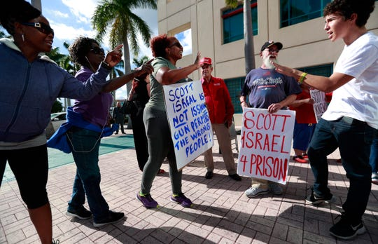 Demonstrators exchange words before the start of a news conference by Florida Gov. Ron DeSantis at the Broward County Sheriff's Office Fort Lauderdale headquarters, Friday, Jan. 11, 2019, in Fort Lauderdale, Fla. DeSantis suspended Broward County Sheriff Scott Israel on Friday over his handling of February's massacre at Marjory Stoneman Douglas High School.