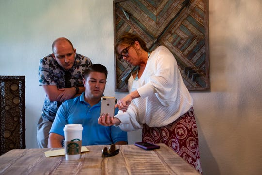 Seasonal homeowners Morgan Stier, left, and Tony Conte watch a video from about three years ago when neighbor Melissa Locast's home had a mold infestation, at Paseo in Fort Myers, on Wednesday, Jan. 9, 2019. Stier and Conte are among several homeowners at the Paseo community who have claimed numerous infrastructural defects and feel that their concerns to have been addressed with only temporary solutions.