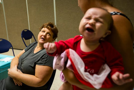 Michele Hall, left, talks to her friend Lindsey Wiggins as 2-month old Zoey cries in her mother's arms near the end of Michele's baby shower on Dec. 15, 2018, at Vineyards Park community center in North Naples.