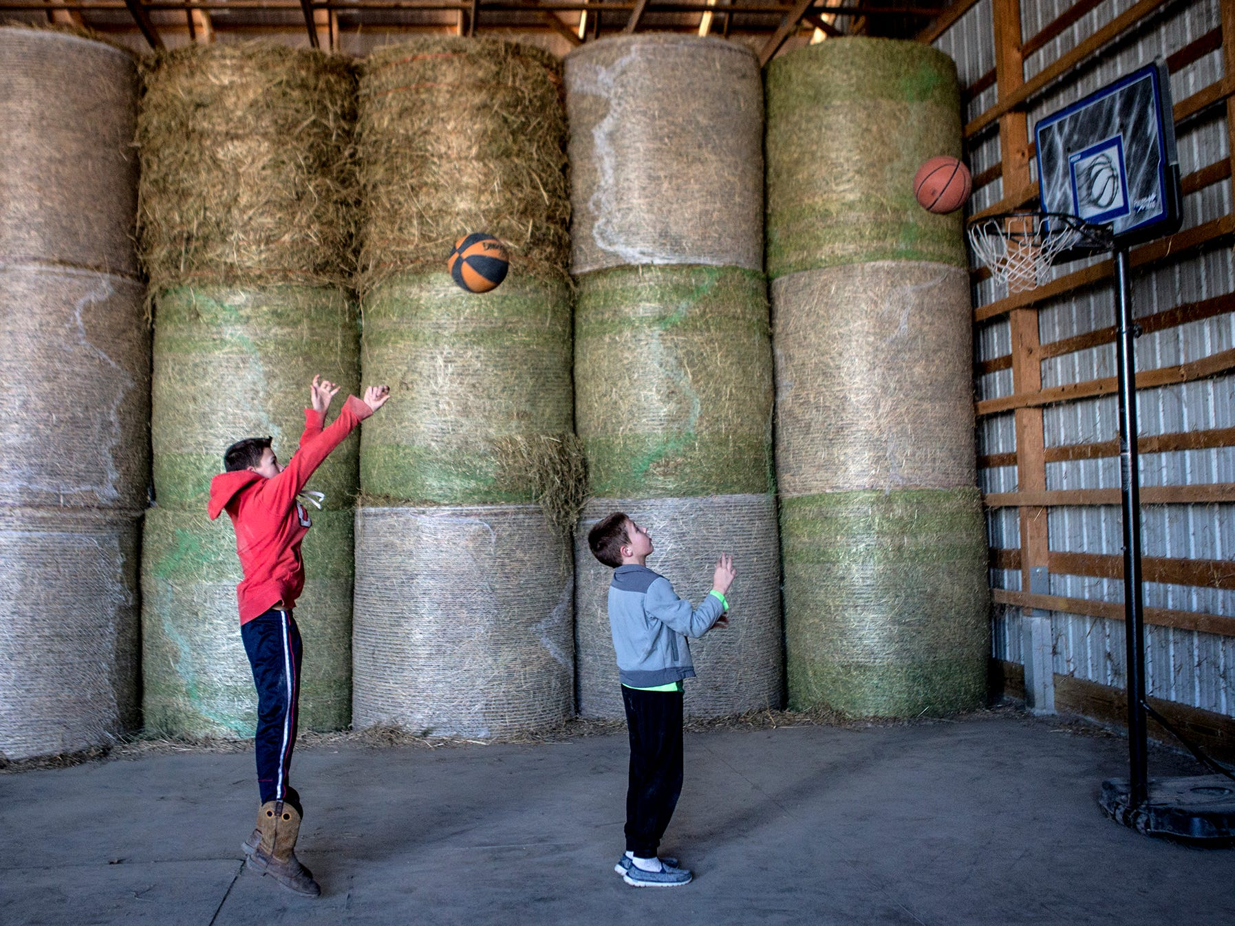 The boys play basketball space that has been made by the sale of hay bales. Both boys play youth basketball.