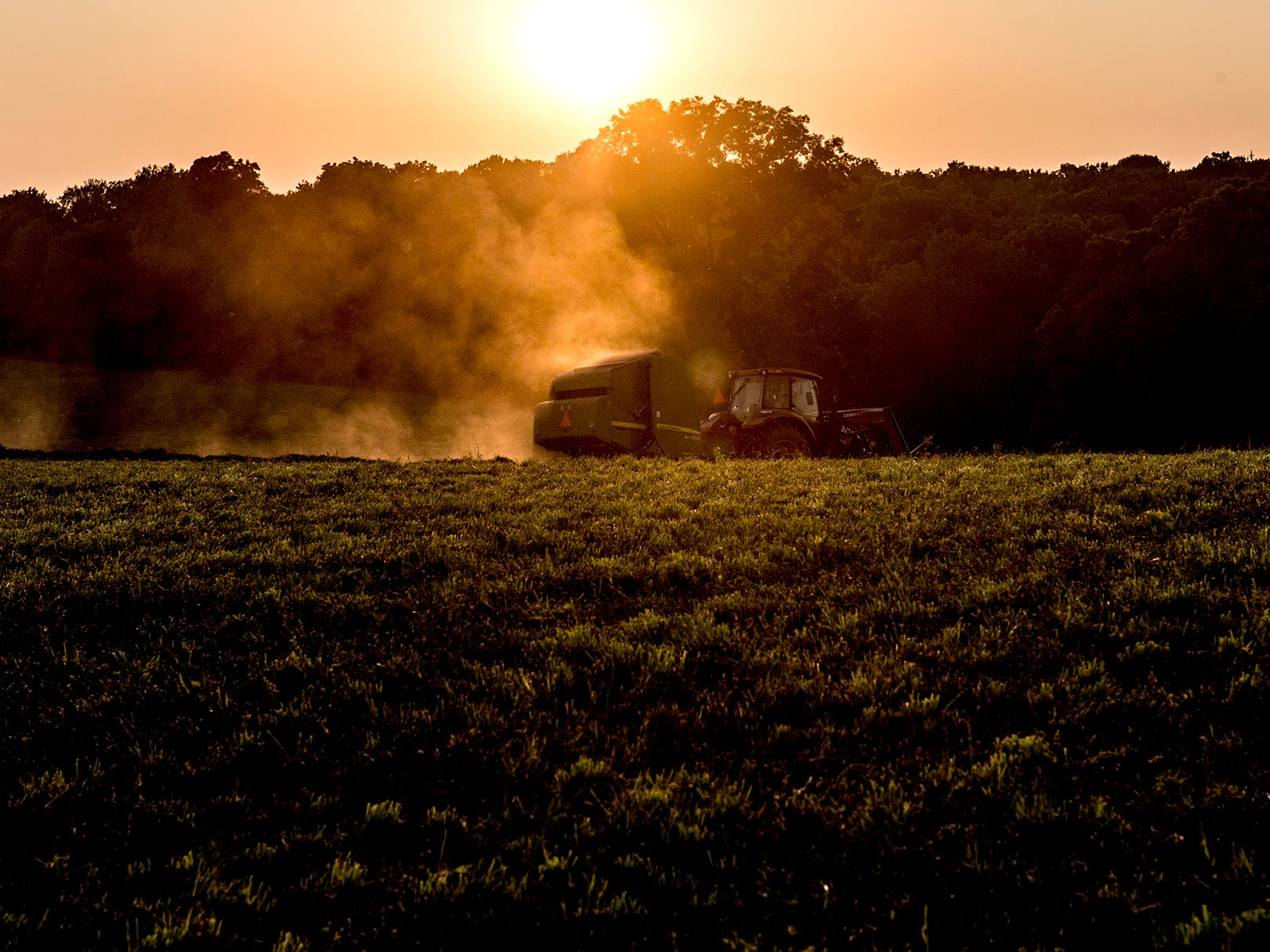 Bailing hay as the sun sets over Utica. This year there were hay shortages bumping the price up for farmers selling. This extra bit of income helped offset losses from the falling price of soy beans due to the trade war with China.