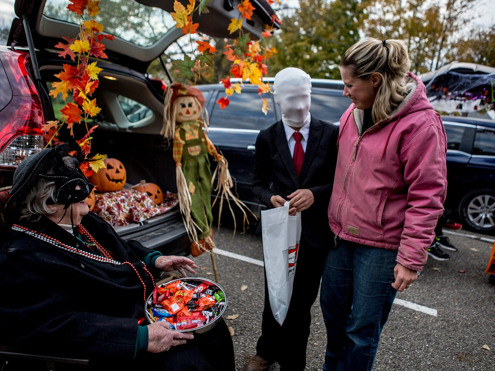 Mamie helps her son, Arthur navigate the cars offering Halloween candy at Utica's Trunk or Treat. Arthur, who went as the slender man, was having trouble seeing through his face mask.