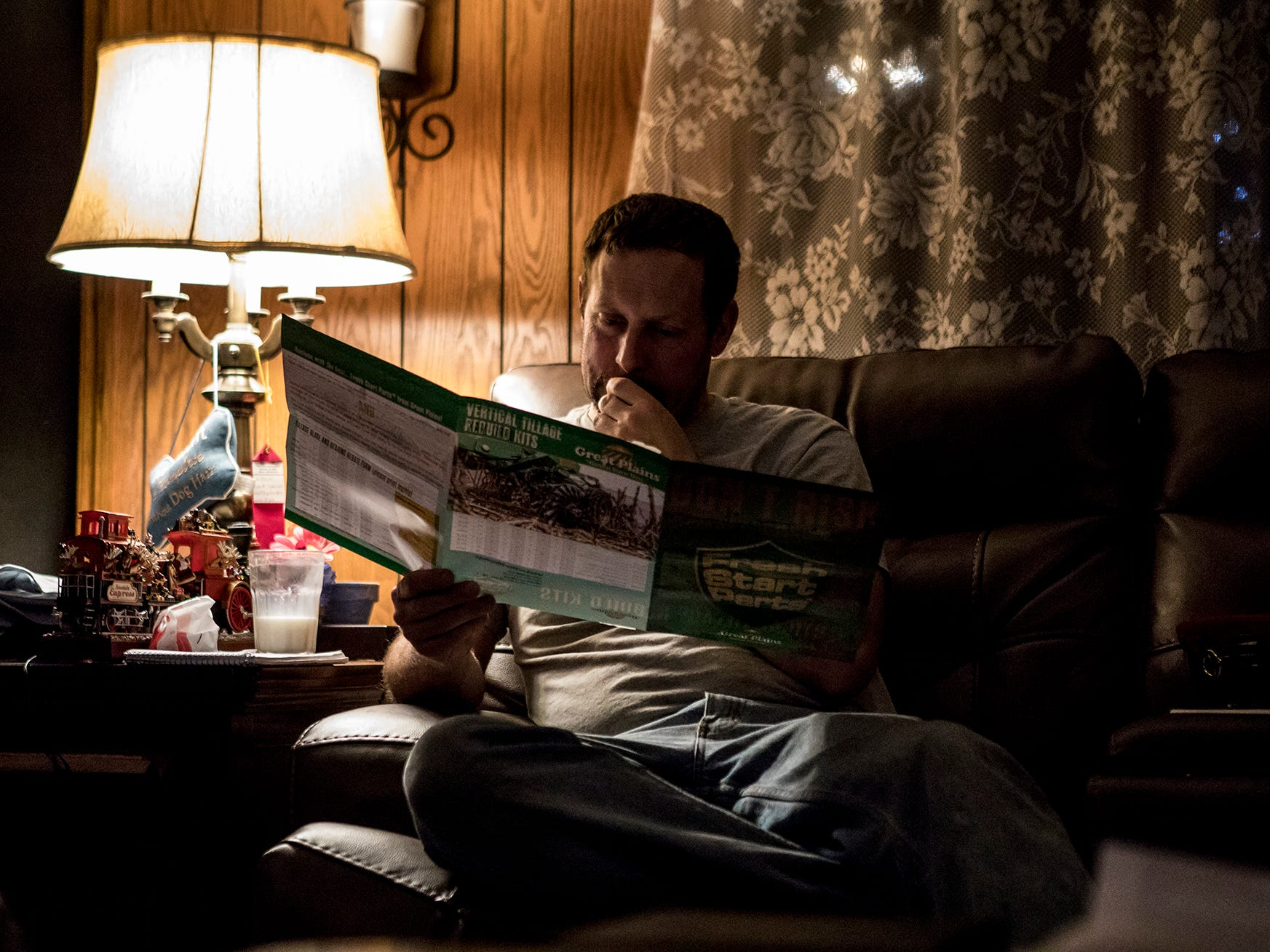 A day after finishing the harvest, Andy sits on his couch reading through newspapers with crop prices and a brochure with hay prices trying to decide if the family should invest in a new hay baler.